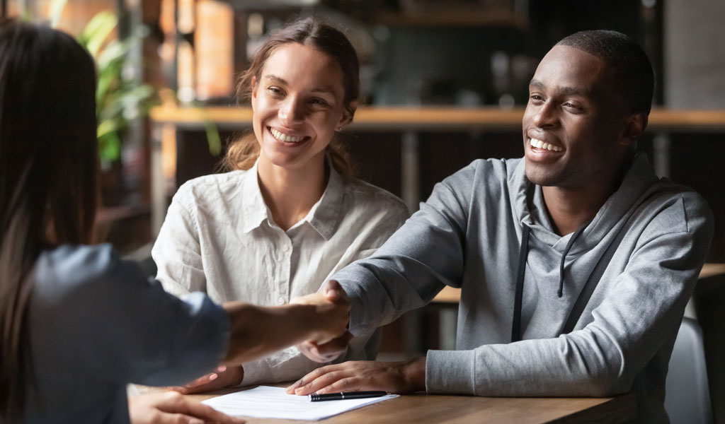 mortgage-advisor-congratulating-a-couple-for-their-purchase