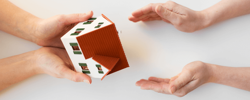 model house being handed from one person to another